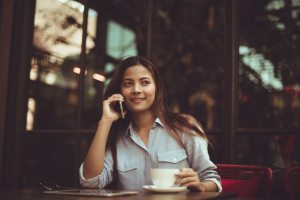 portrait-of-young-woman-using-mobile-phone-in-cafe-323503